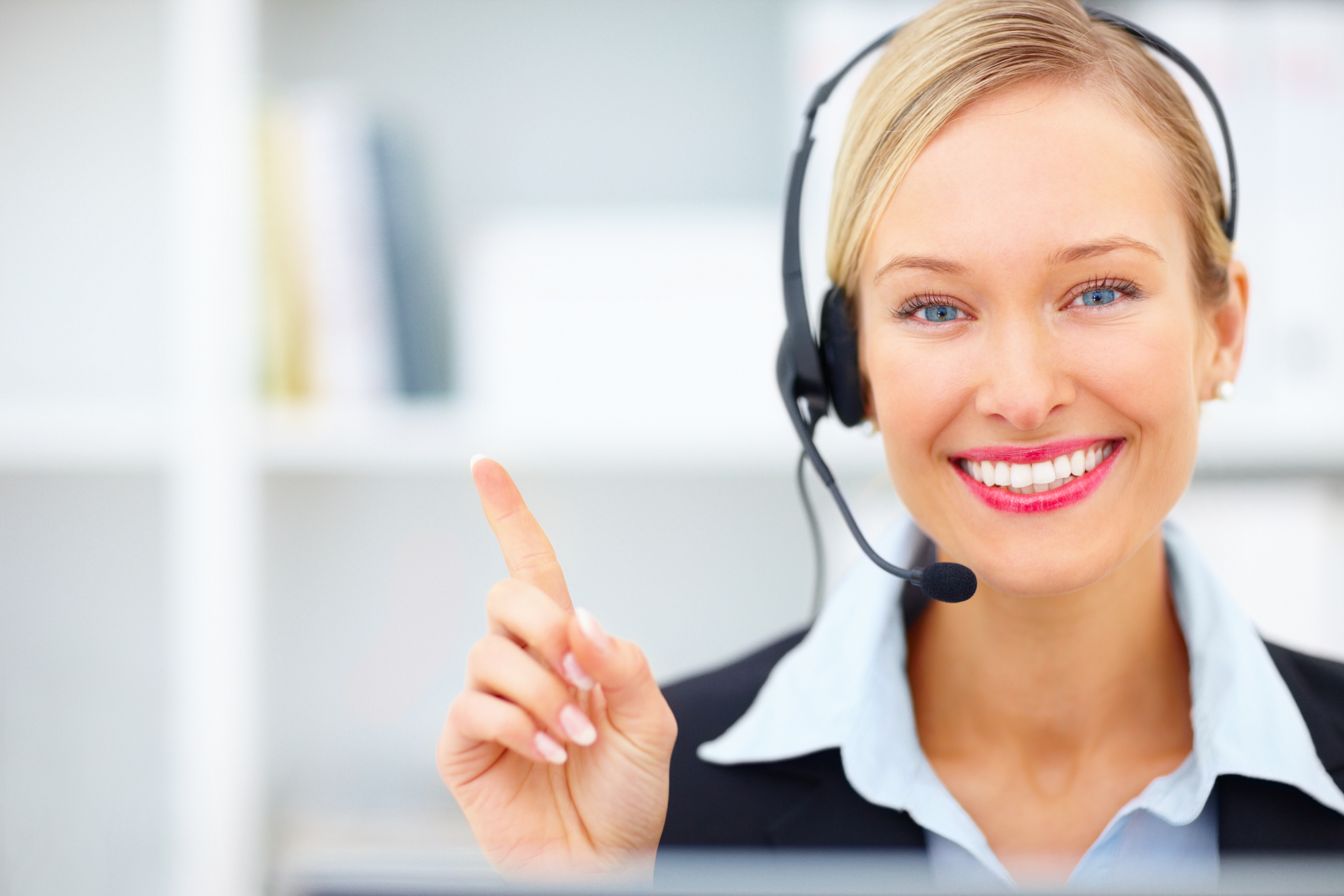 Young receptionist with headset pointing towards copyspace